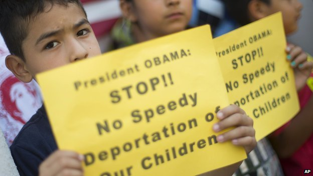 A child holds up a sign telling President Obama not to deport children detained at the US southern border.