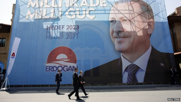 Security officers walk pass by a huge election banner of Mr Erdogan in Istanbul (11 July 2014)