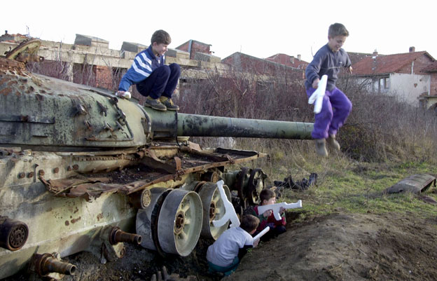 Children play on a tank in Kosovo