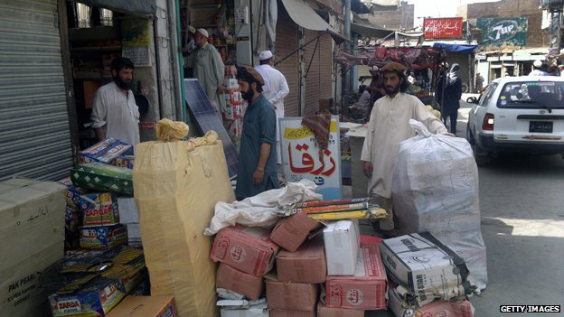 Pakistani shopkeepers pack goods from their shop as they prepare to flee from a military operation in North Waziristan tribal agency, in Miranshah on June 18, 2014
