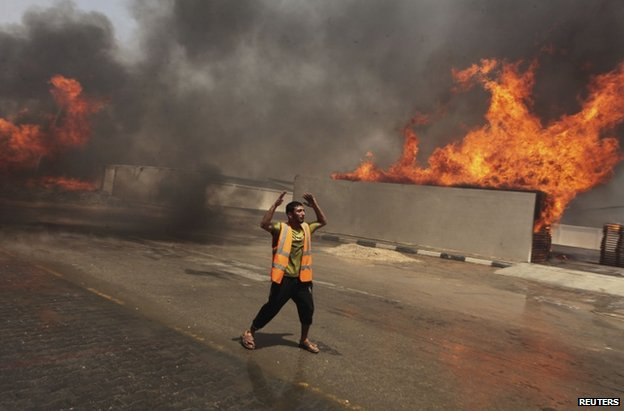 A man reacts as a fire burns in Gaza City, 12 July