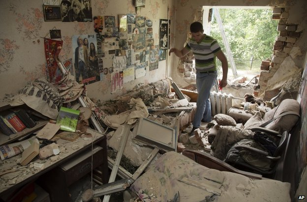 A man inspects his ruined flat in Marinka, Donetsk, 12 July