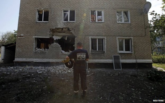 A rescue worker outside a damaged block of flats in Marinka, Donetsk, 12 July