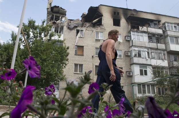 A man passes a damaged block of flats in Marinka, Donetsk, 12 July