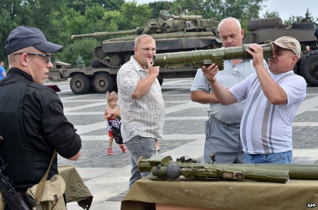 Ukrainian civilians in Kiev inspect weapons said to have been captured from the rebels, 12 July