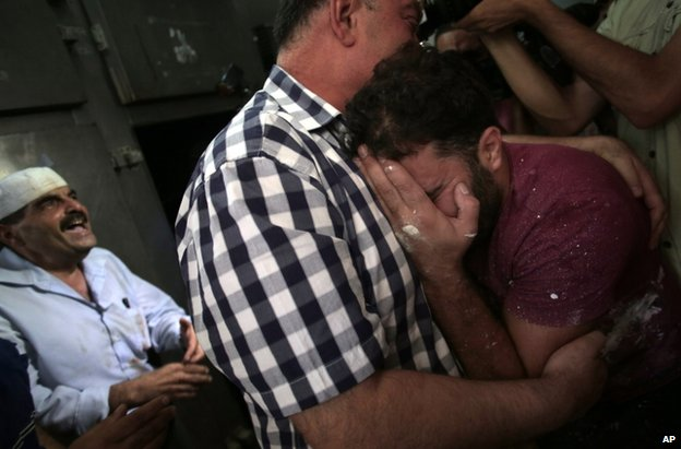 Palestinians mourn in a morgue in Gaza City, 12 July