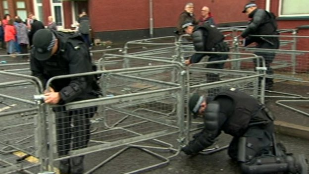Police remove barriers that prevented the Orange return parade from passing along a stretch of the Crumlin Road in north Belfast