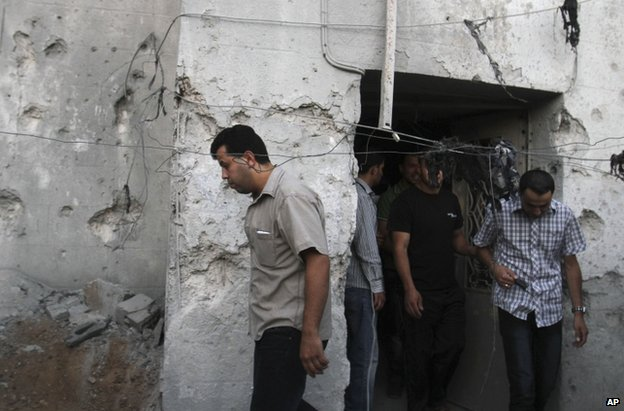 Palestinians pass a damaged house after a Palestinian rocket hit Hebron in the West Bank, 12 July