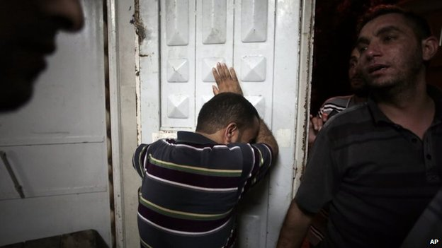 Palestinians mourn their relatives in the morgue of the Shifa hospital in Gaza City, 12 July 2014