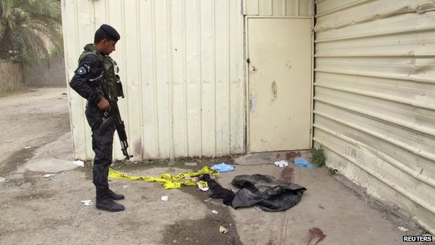An Iraqi policeman looks at blood marks on the ground near an apartment building where the shooting occurred