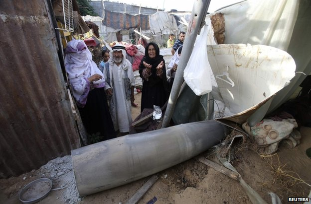 Palestinians crowd around a missile said to have been fired by Israel at a target in Rafah, Gaza Strip, 13 July