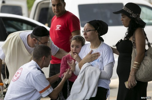 An Israeli mother and daughter are treated for shock after a rocket attack on Ashkelon, 13 July