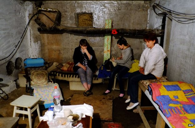Civilians sit in a bomb shelter in Donetsk, eastern Ukraine, 13 July