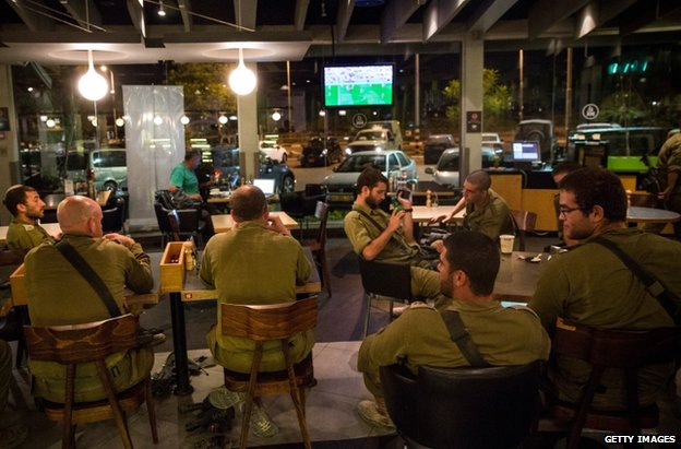 Israeli soldiers watch the World Cup Final in a cafe in Sderot, 13 July