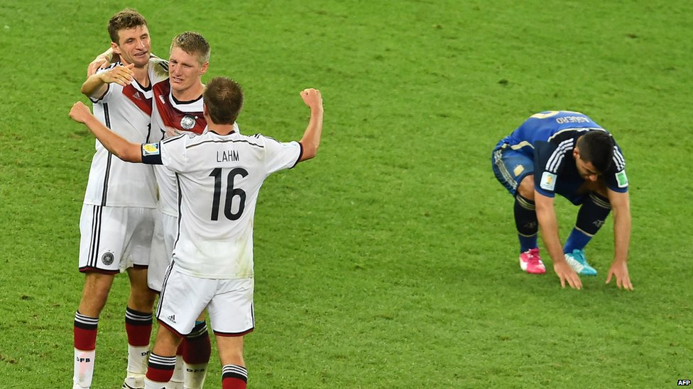 Germany's forward Thomas Mueller, midfielder Bastian Schweinsteiger and and captain Philipp Lahm celebrating victory as Argentina's forward Sergio Aguero hangs his head