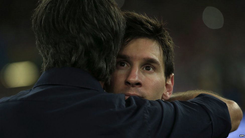 Argentina's forward and captain Lionel Messi (R) is embraced by Germany's coach Joachim Loew