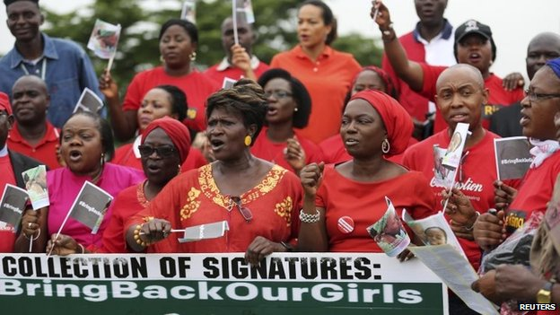 "File photo: People wearing red hold a banner at a speak-out session of a ""bring back our girls"" rally in Lagos, Nigeria, 7 June 2014"