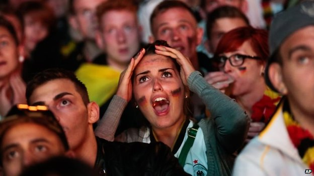 "German fans react as they watch a live broadcast of the final match between Germany and Argentina at the soccer World Cup 2014 at a public viewing area called ""Fan Mile"" in Berlin, 13 July 2014"
