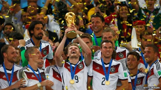 Andre Schuerrle of Germany raises the World Cup trophy and celebrates with teammates after defeating Argentina 1-0 in extra time during the 2014 FIFA World Cup Brazil Final match between Germany and Argentina at Maracana in Rio de Janeiro, Brazil, 13 July 2014