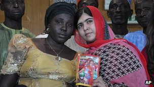 Pakistani activist Malala Yousafzai holds a picture of kidnapped schoolgirl Sarah Samwell with her mother Rebecca, during a visit to Abuja, Nigeria, 13 July 2014