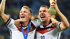Bastian Schweinsteiger and Lukas Podolski of Germany celebrate with the World Cup trophy