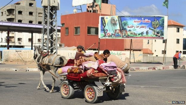 Palestinians, who fled their homes in the northern border town of Beit Lahiya, ride a horse cart on their way to stay at a United Nations-run school (14/07/14)