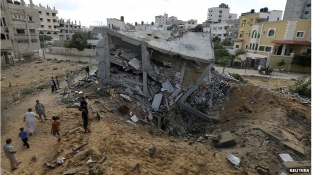 Palestinians gather around the remains of a house which police said was destroyed in an Israeli air strike in Gaza City July 14, 2014