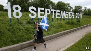 "Ronnie Anderson from Edinburgh waves a Saltire flag beside the ""18 September 2014"" sign outside the Scottish Parliament"