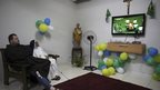 A priest from the Franciscan order and a nun from the enclosed monastery of Imaculada Conceicao watch on television as Brazil's Neymar grimaces as he is carried off the pitch after being injured in the 2014 World Cup quarter-final