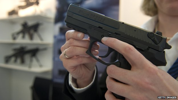 An employee of German-Swiss weapon manufacturer SIG Sauer holds a SIG Sauer SP 2022 9mm pistol at the SIG Sauer stand at the European Police Congress in Berlin on 15 February, 2011.