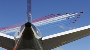 The Royal Air Force (RAF) Red Arrows aerobatic display team perform a fly past Farnborough Airport