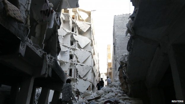 People walk through the rubble of collapsed buildings in Aleppo, Syria