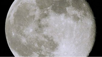 The moon fills the photograph. Craters and details on the surface of the moon can be seen.