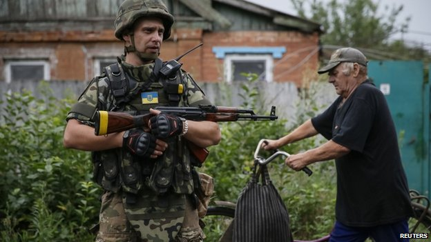 A local resident pushes a bicycle past a Ukrainian soldier in the eastern Ukrainian village of Semenivka, near Sloviansk. Photo: 14 July 2014