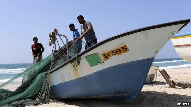 Fishermen repair their nets on a beach in the southern Gaza Strip (6 July 2014)
