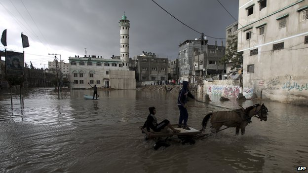 Palestinian youths cross a flooded street on a cart following heavy rainfall in Gaza City on 13 December 2013