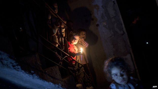 Palestinian children stand near a candle during a power cut in Beit Lahia (12 November 2013)