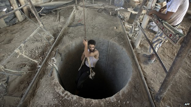 Palestinian man is lowered into a smuggling tunnel beneath the Gaza-Egypt border (11 September 2013)