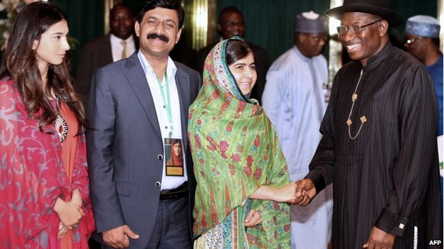Pakistani education activist Malala Yousafzai (2nd R) shakes hands on 14 July 2014 with Nigerian President Goodluck Jonathan (R) next to her father, Ziauddin Yousafzai (2nd L), and Malala Fund committee member Shiza Shahid (L) at the State House in Abuja.