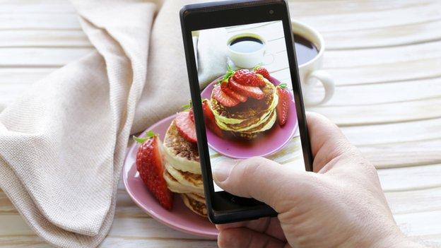 A cellphone takes a picture of a pancake breakfast.