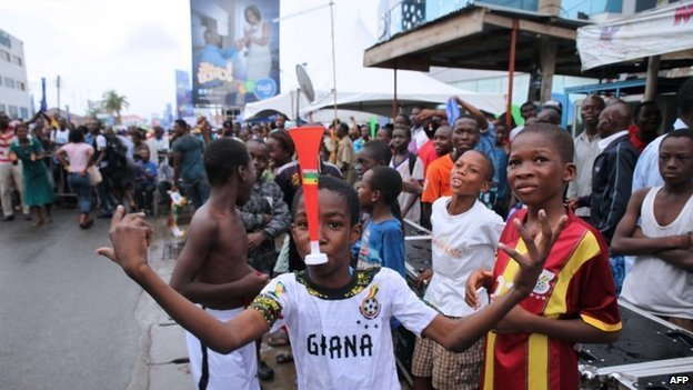 A child poses with a vuvuzela as Ghana supporters react while watching the FIFA World Cup 2014 football match between Ghana and Portugal on 26 June 2014 in Accra.