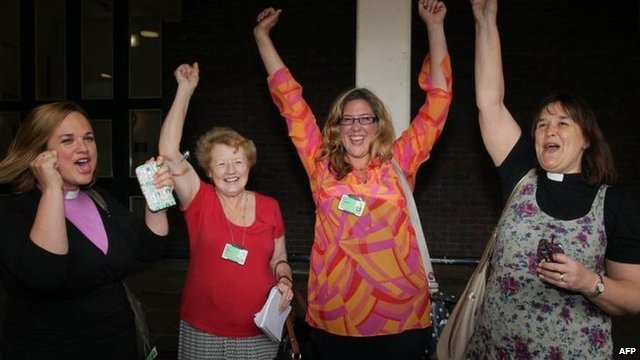 Female members of the clergy celebrate after members voted to approve the creation of female bishops at the Church of England General Synod in York,
