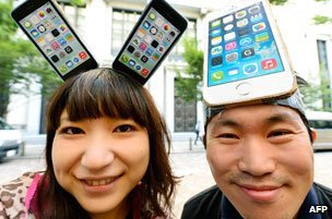 Young people wearing hats in the shape of smartphones