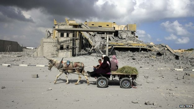 Palestinians ride a donkey cart past a damaged building in Rafah in the southern Gaza Strip July 15, 2014.