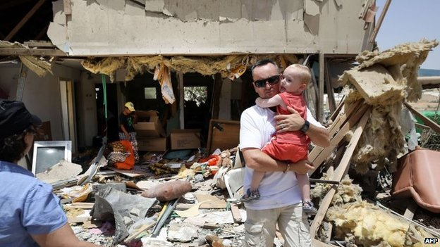 Residents of the southern Israeli city of Beersheba inspect the damage to a house in their city on July 12, 2014, after it was hit by a rocket fired during the night from the Gaza Strip