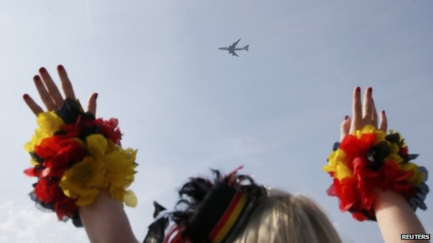 "Fans cheer as the plane carrying the German national soccer team flies over the ""fan mile"" public viewing zone before landing at Tegel airport (14 July 2014)"