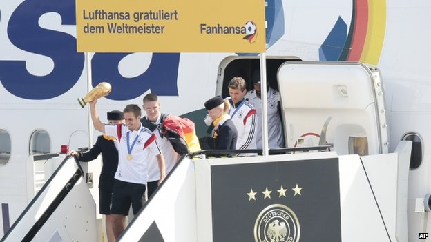 Members of the German team with the World cup in hand get off their plane after it arrived in Berlin