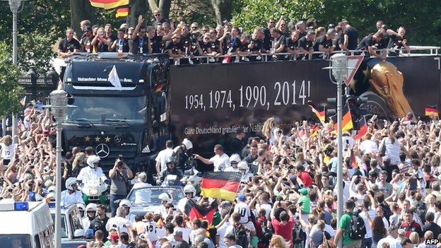 German fans cheer as the national team rides in an open-deck bus in central Berlin (14 July 2014)