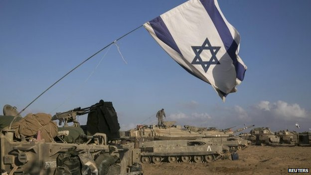 Israeli tanks and armoured personnel carriers (APCs) are seen at a staging area outside the central Gaza Strip July 15, 2014.