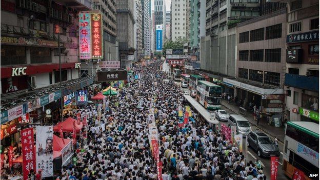 Demonstrators march during a pro-democracy rally seeking greater democracy in Hong Kong on 1 July 2014 as frustration grows over the influence of Beijing on the city.